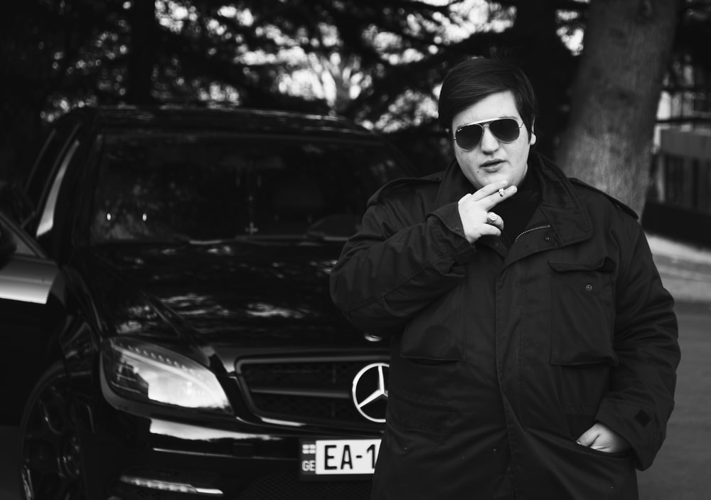 grayscale photo of man wearing sunglasses and jacket