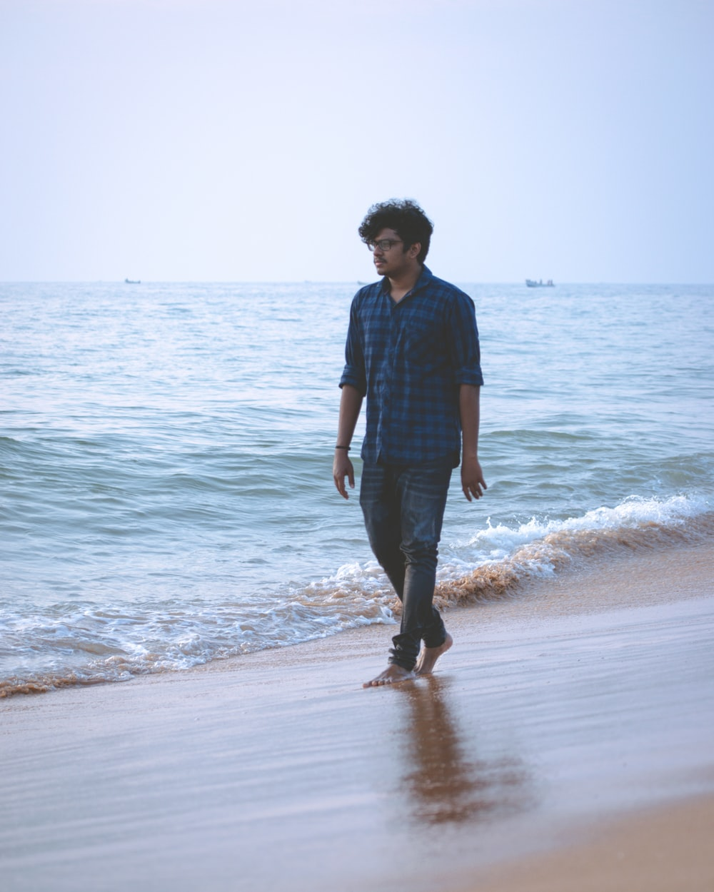 man in black dress shirt and blue denim jeans standing on seashore during daytime