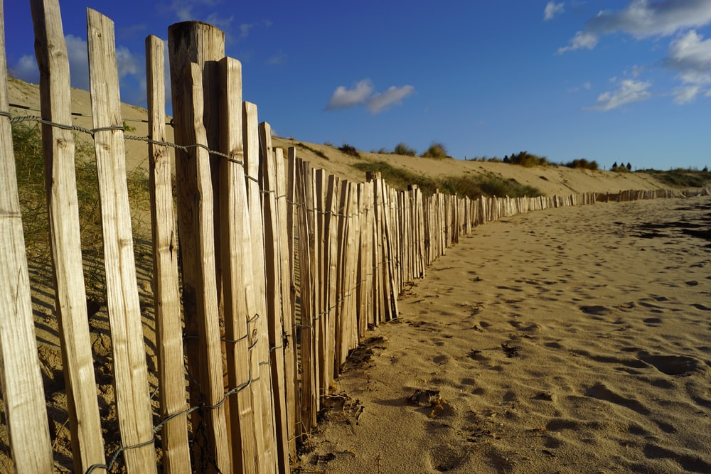 brown wooden fence on brown sand under blue sky during daytime