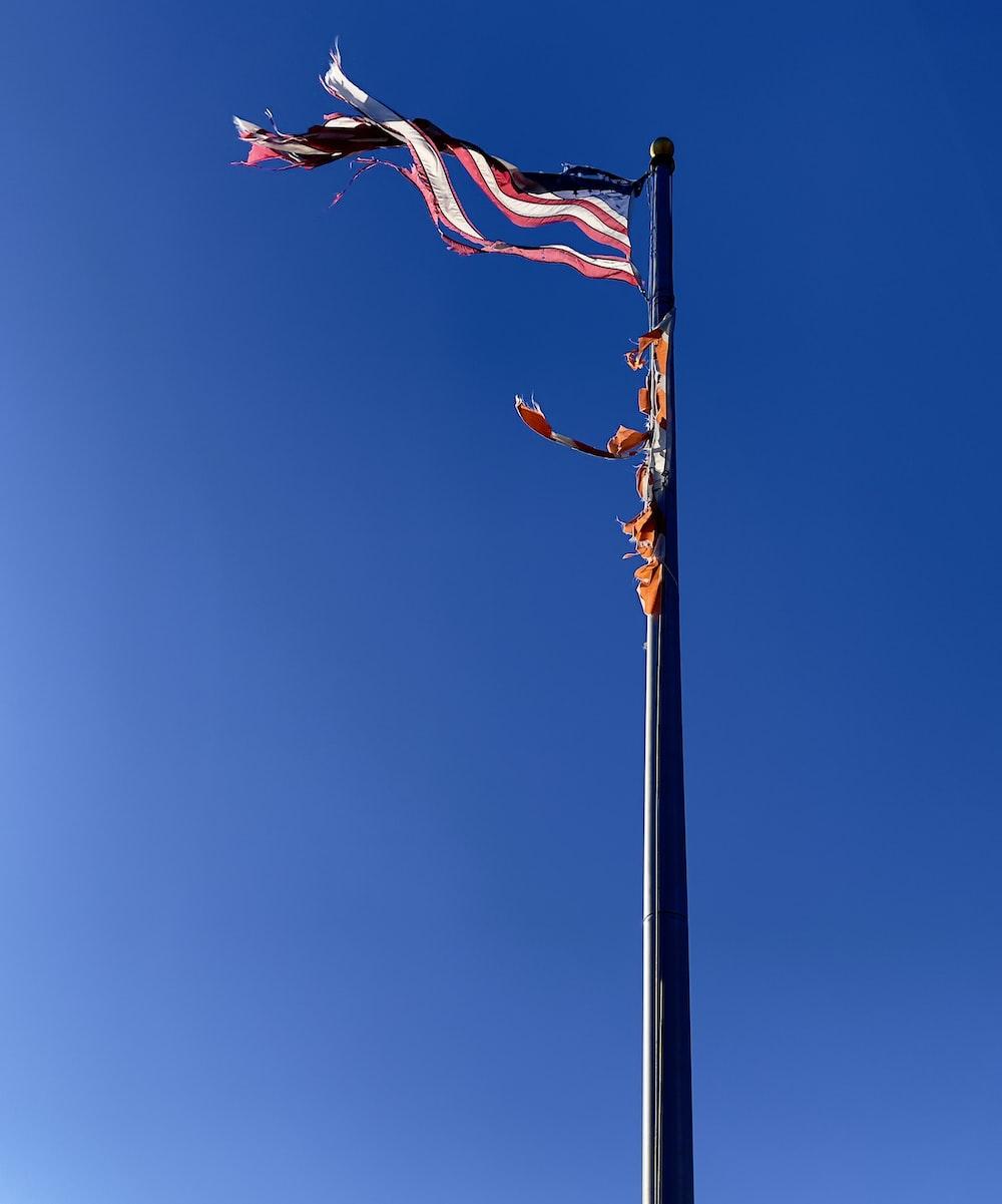 flag of us a on pole under blue sky