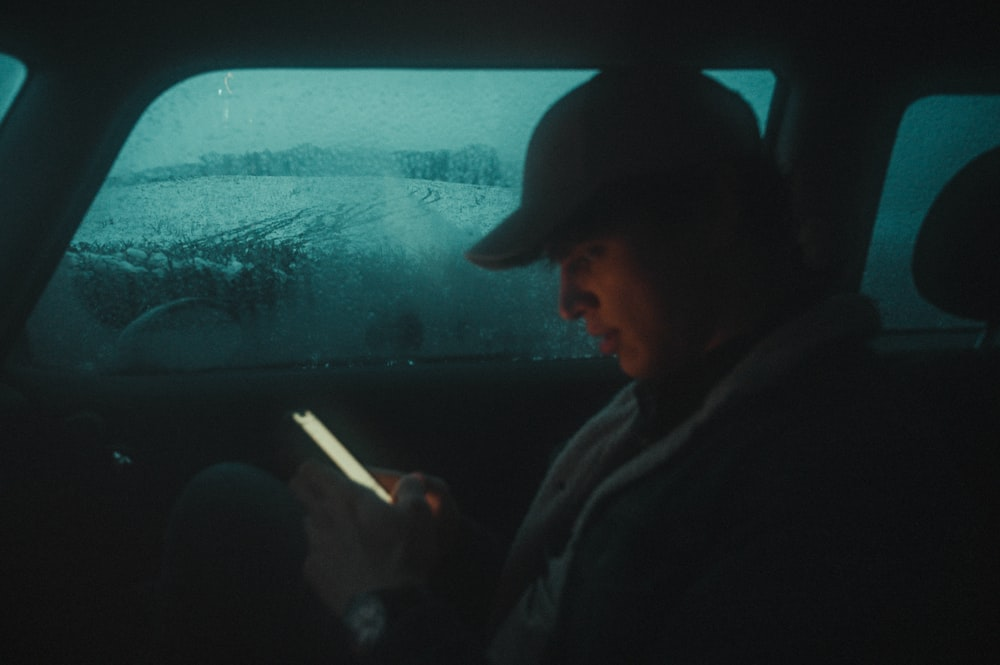 man in black jacket and black cap looking at the window