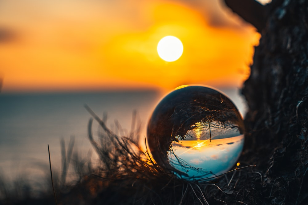 clear glass ball on green grass during sunset
