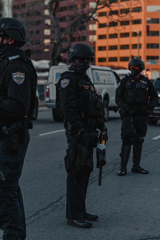 2 police men walking on the street during daytime