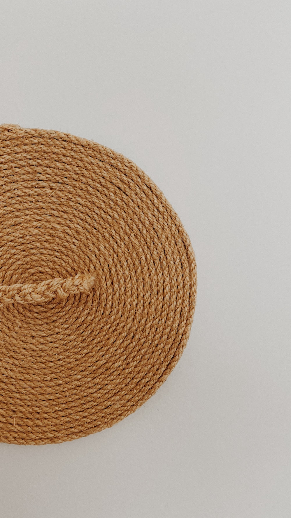 brown woven round basket on white surface
