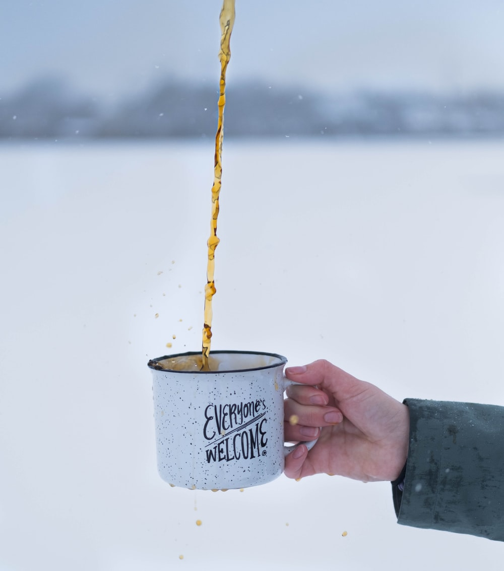 person holding white and blue ceramic mug with yellow string