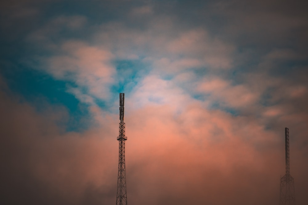silhouette of tower under orange and blue sky