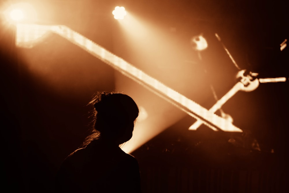 silhouette of person standing near stage light