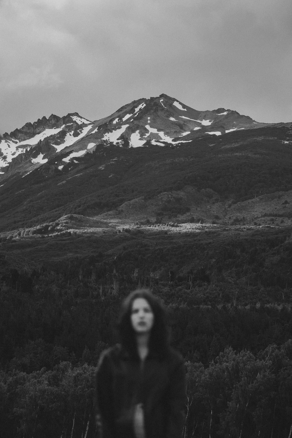 grayscale photo of woman standing on grass field near mountain