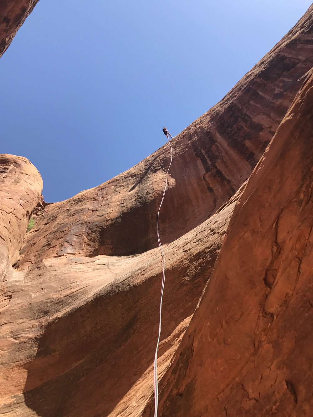 person climbing on brown rock formation during daytime