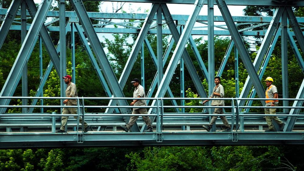 man in white shirt standing on gray metal bridge