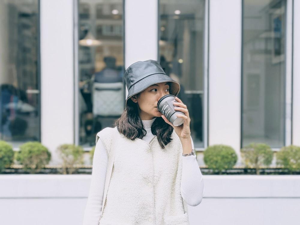 woman in white sweater wearing black cap holding black dslr camera