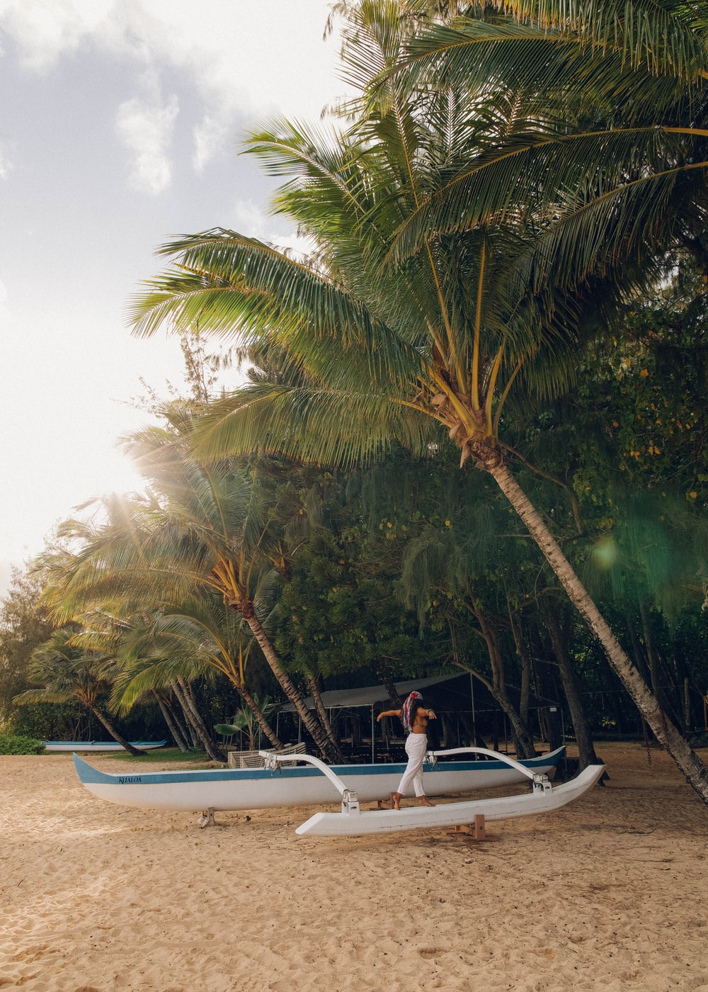 woman in white shirt sitting on white surfboard near palm trees during daytime