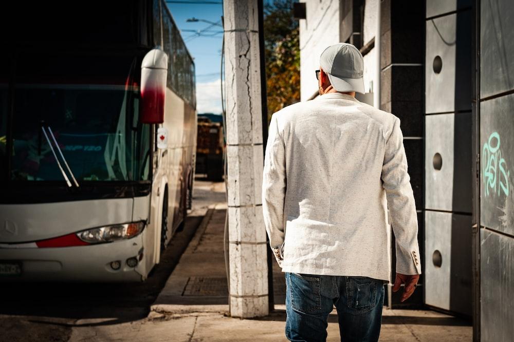 man in white hoodie standing near white van during daytime