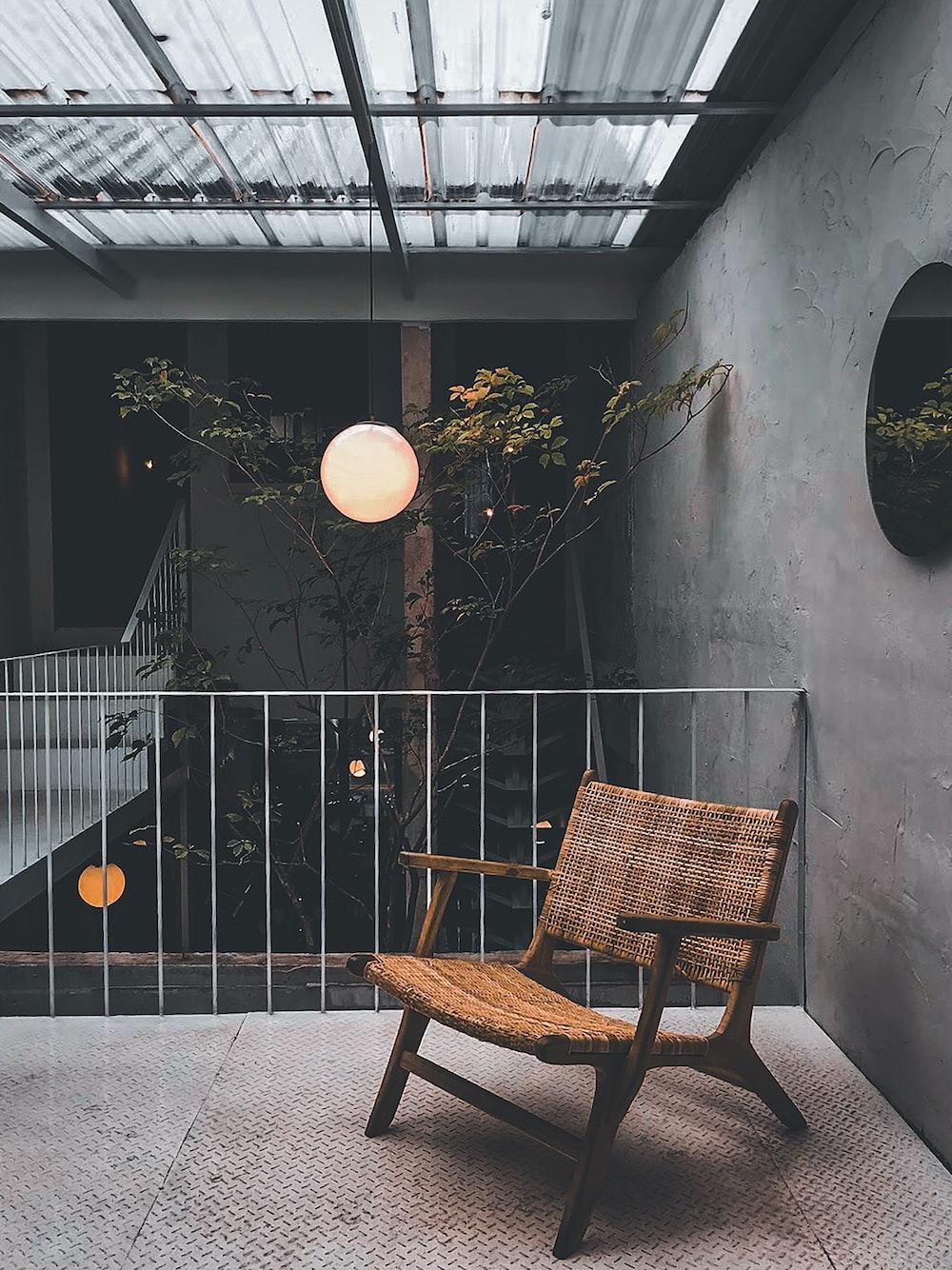brown wooden armchair beside black metal fence