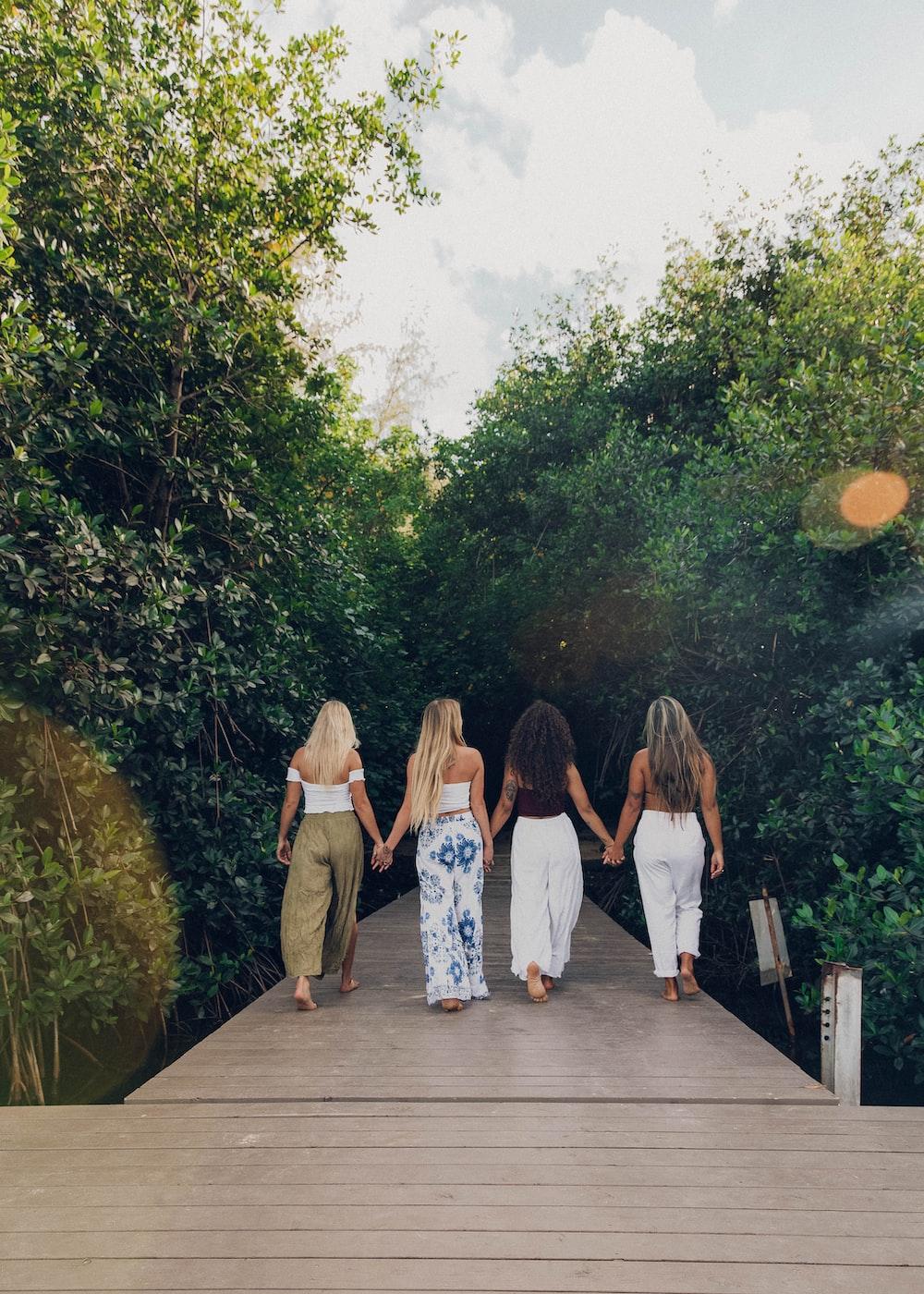 3 women standing on wooden bridge