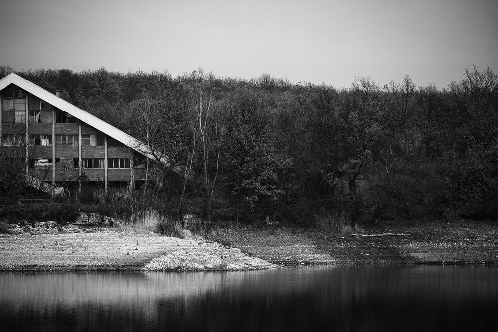 grayscale photo of house near river