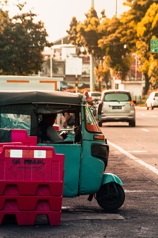 man in blue t-shirt driving pink car during daytime