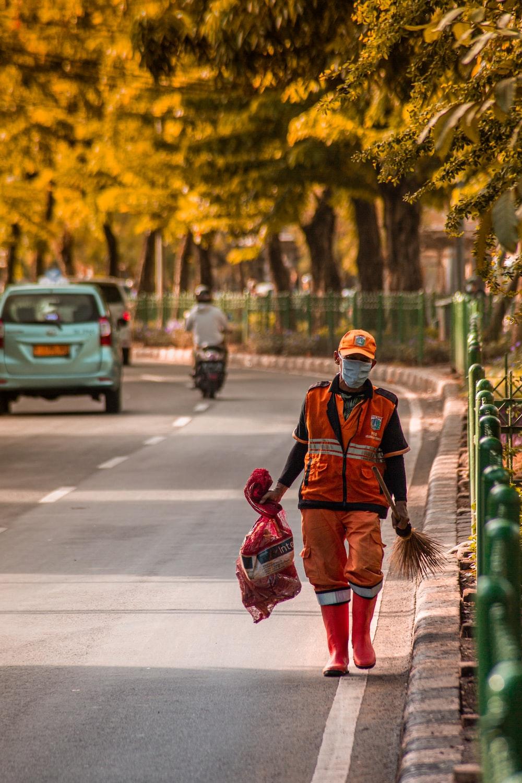 man in red and black jacket walking on sidewalk during daytime