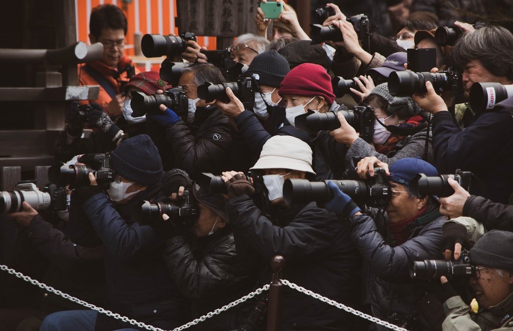 people in black jacket taking photo