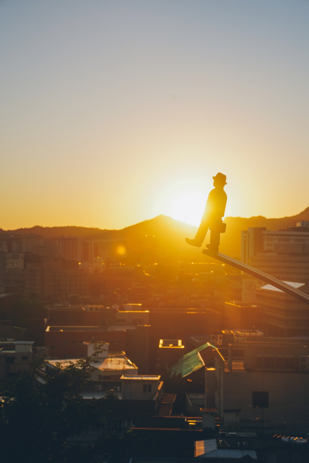 silhouette of man standing on top of building during sunset