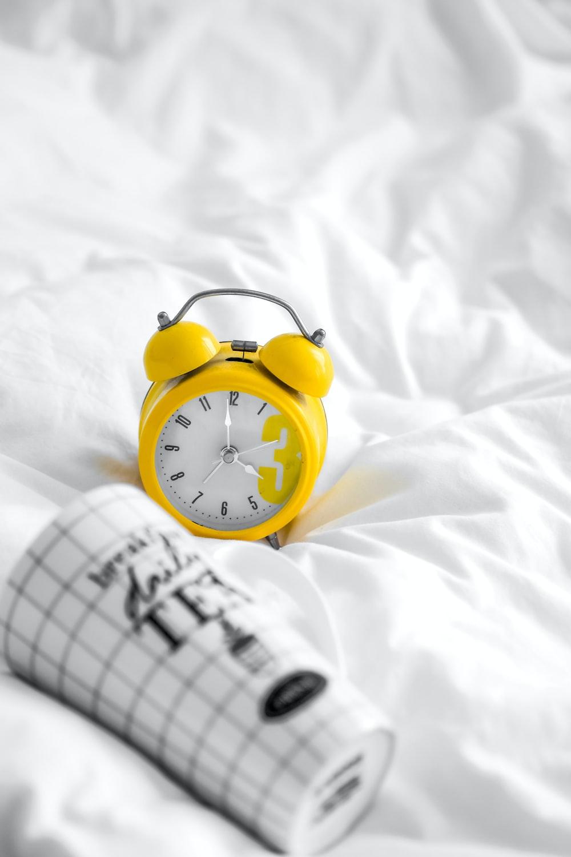 yellow and white analog alarm clock at 10 10