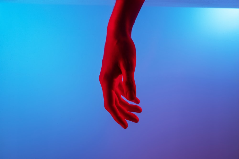 persons left hand on blue surface