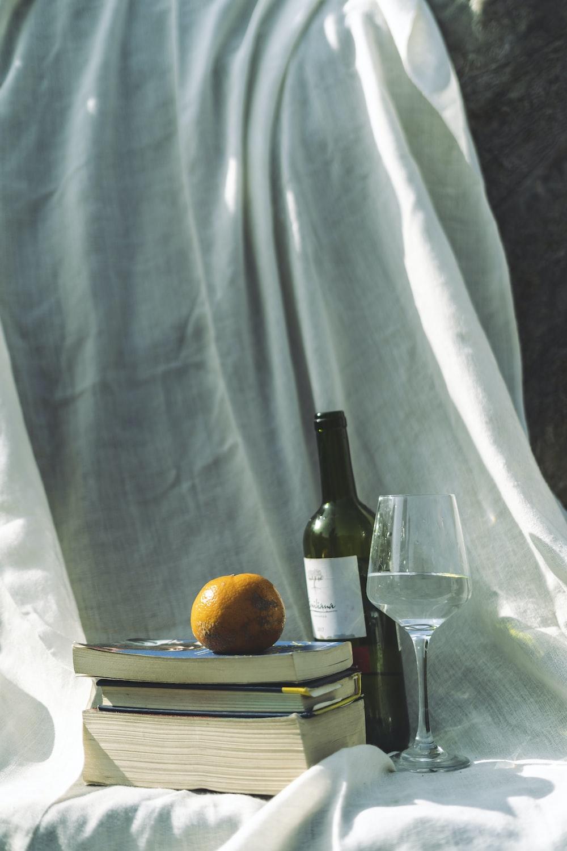 orange fruit beside wine bottle on table