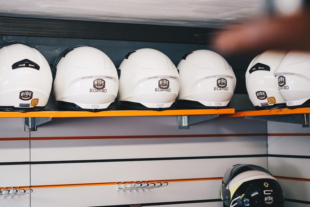 white and black helmet on brown wooden shelf