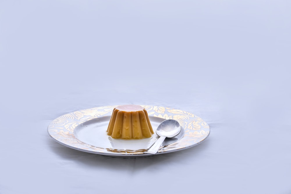 brown and white ceramic saucer with stainless steel spoon