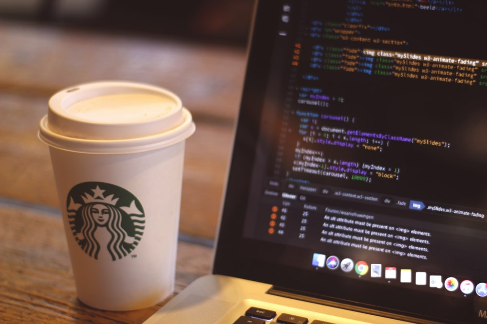 white starbucks cup beside black and silver laptop computer