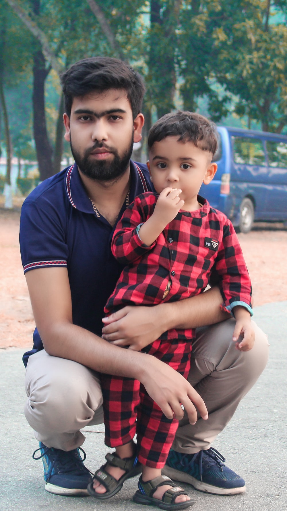 man in blue crew neck t-shirt sitting beside boy in red and black plaid button
