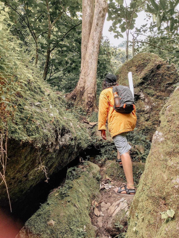 man in orange jacket climbing on brown rock