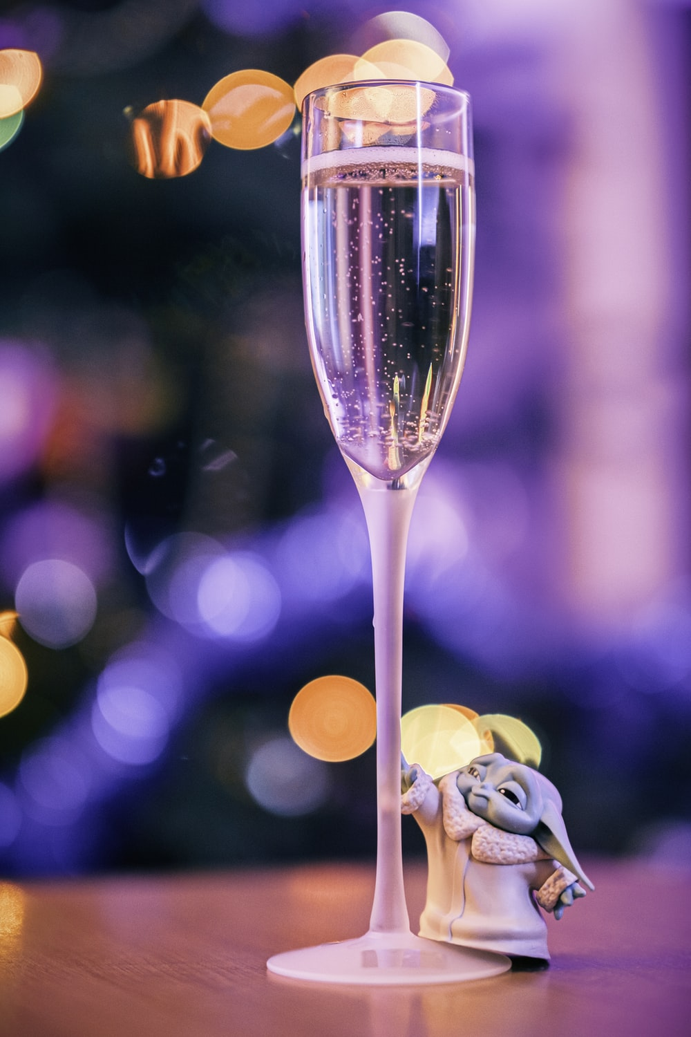 clear long stem wine glass with yellow light bokeh