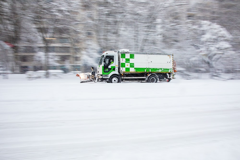green truck on snow covered road during daytime