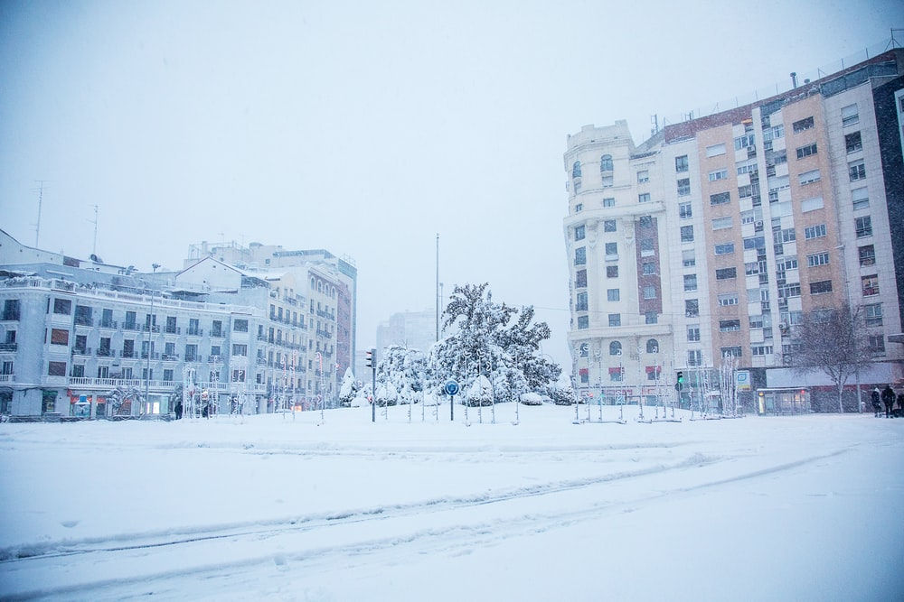white snow covered field near white concrete building during daytime