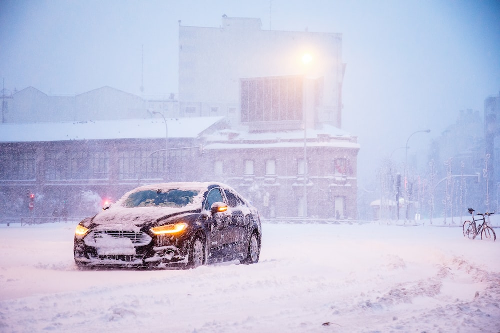 yellow and black sports car on snow covered road during daytime