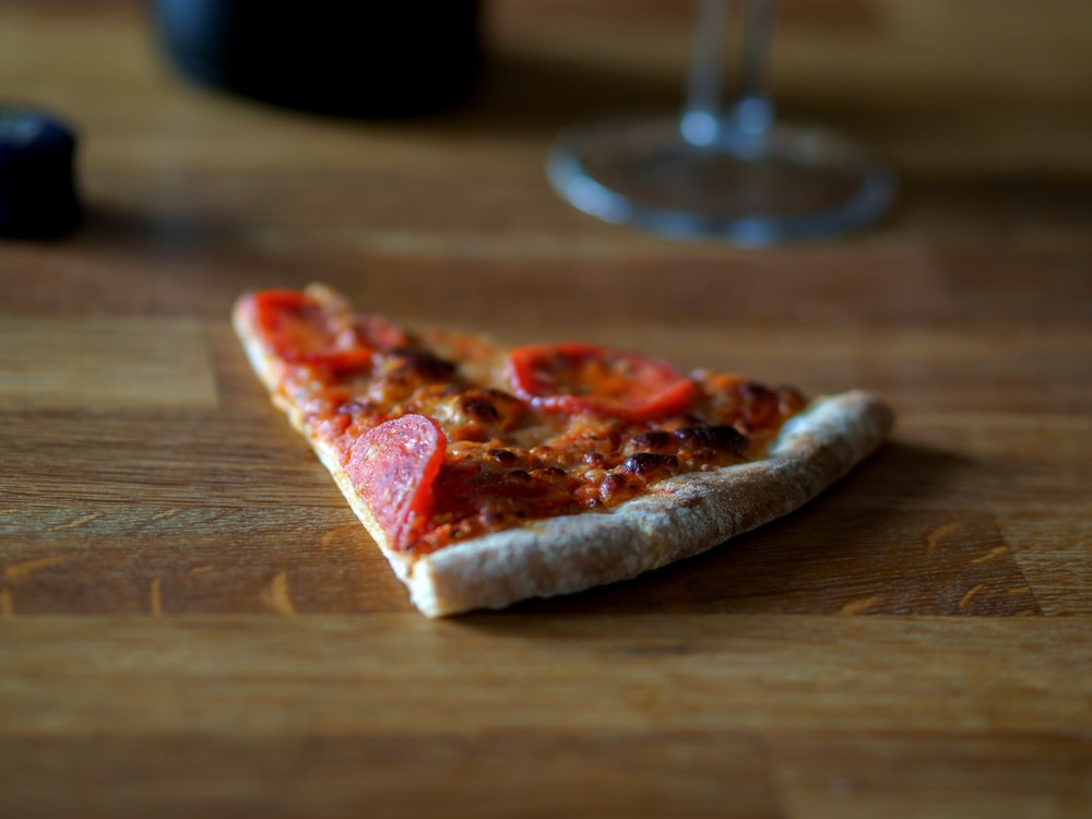 sliced pizza on brown wooden table