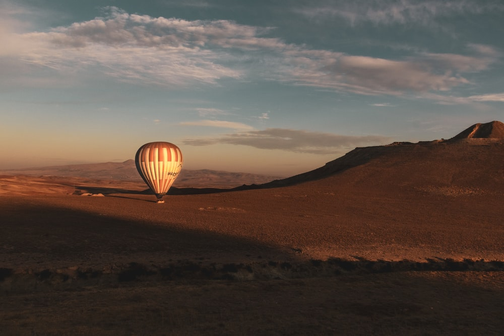 hot air balloon on brown field under blue sky during daytime