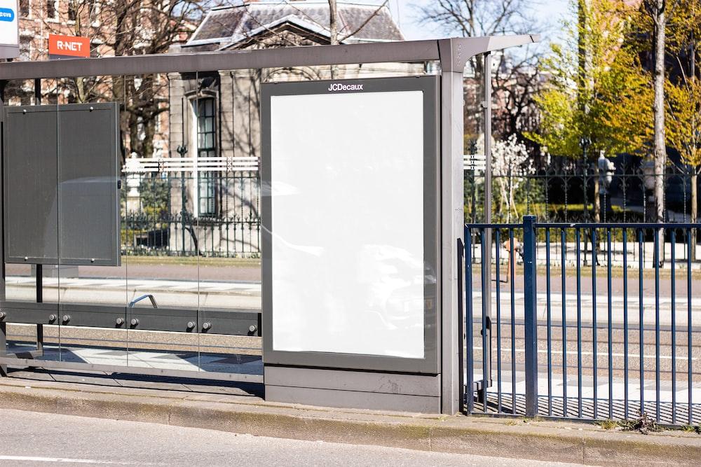 white board on black metal fence
