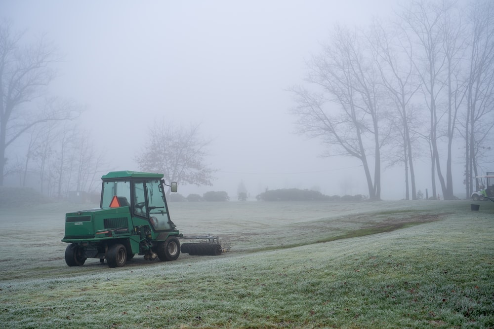 green tractor on green grass field during daytime