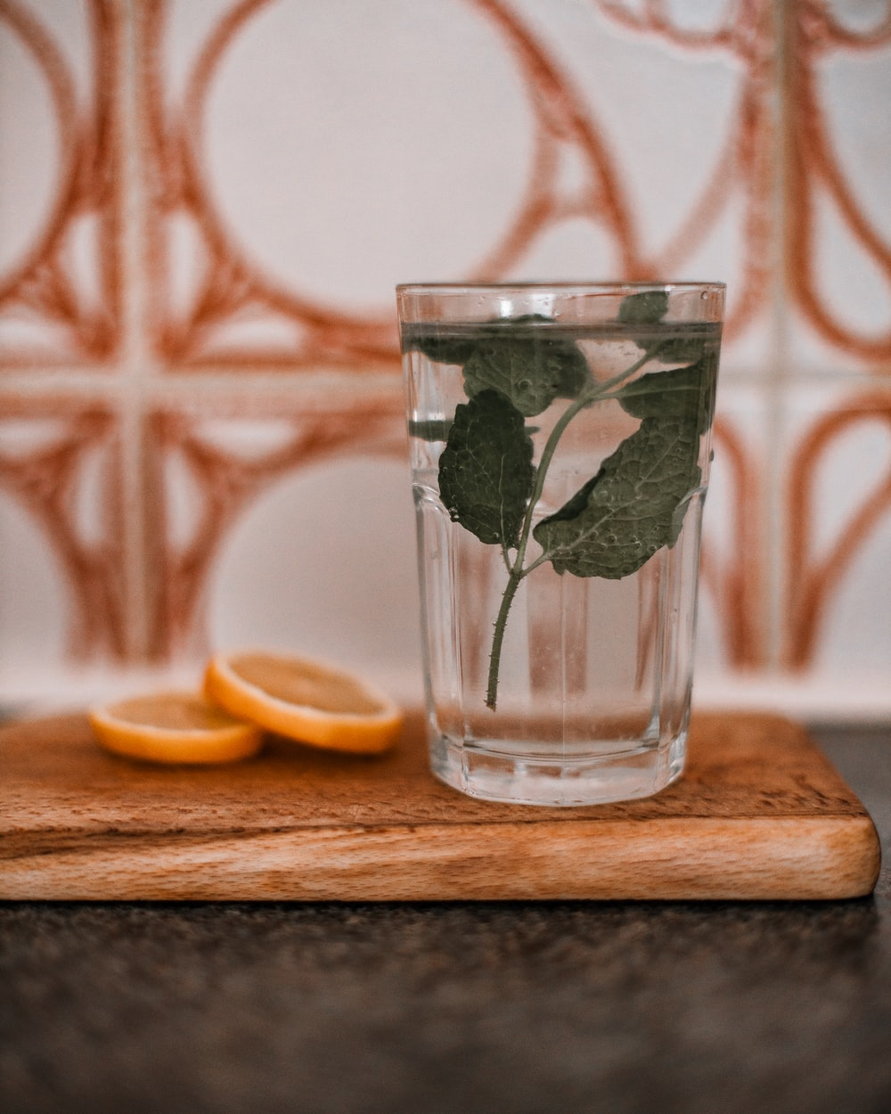 clear drinking glass with water and sliced lemon on brown wooden chopping board