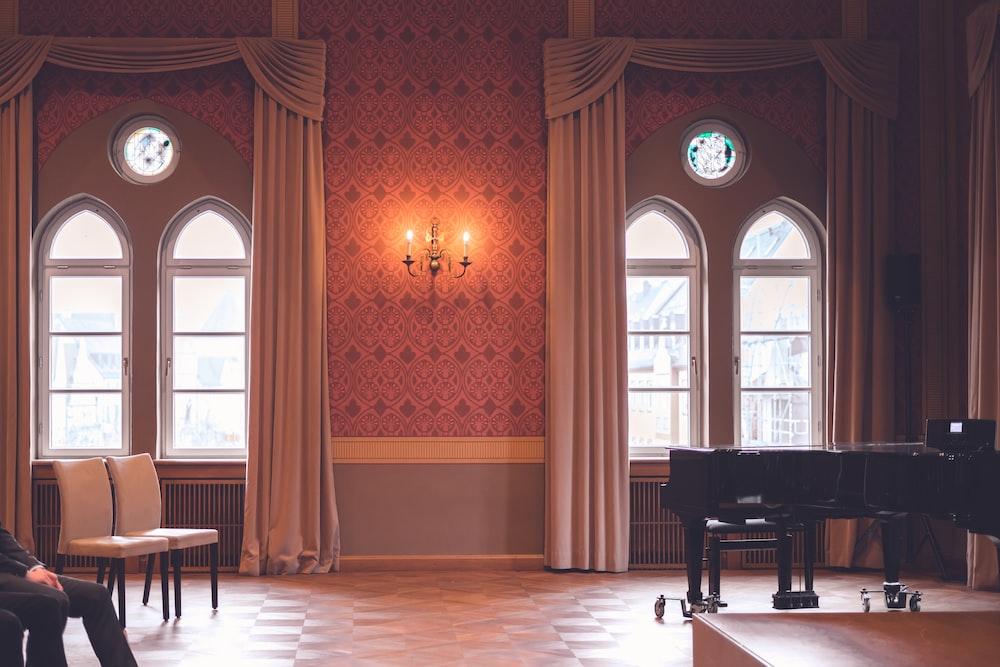 black grand piano near brown wooden door