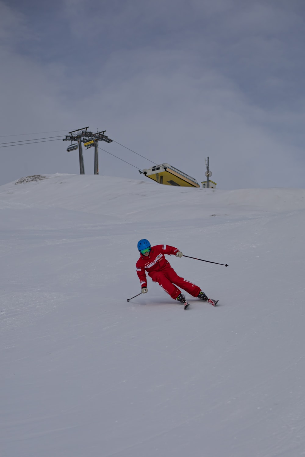 person in red jacket and red pants riding snow ski