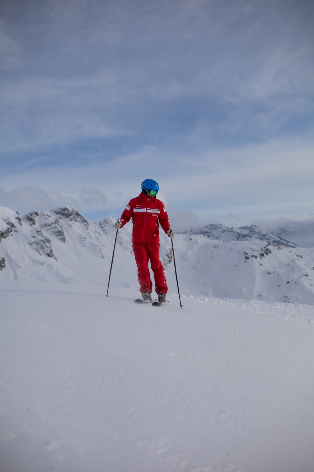 person in red jacket and black pants riding ski blades on snow covered mountain during daytime
