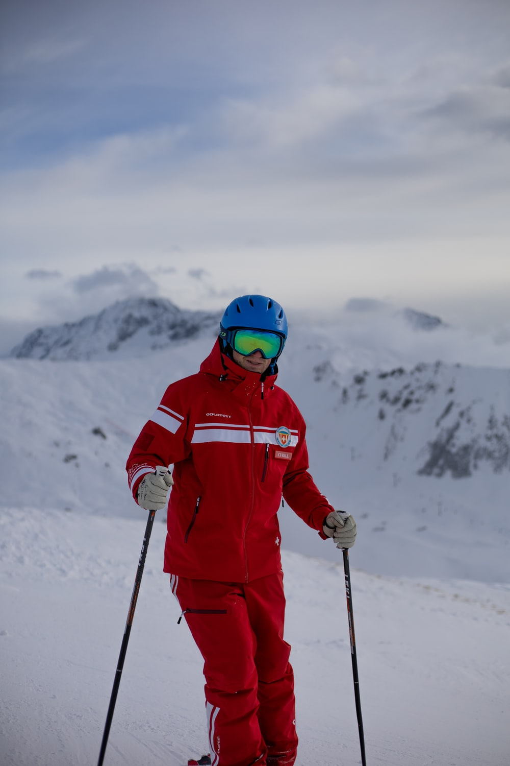 person in red jacket and helmet standing on snow covered ground during daytime