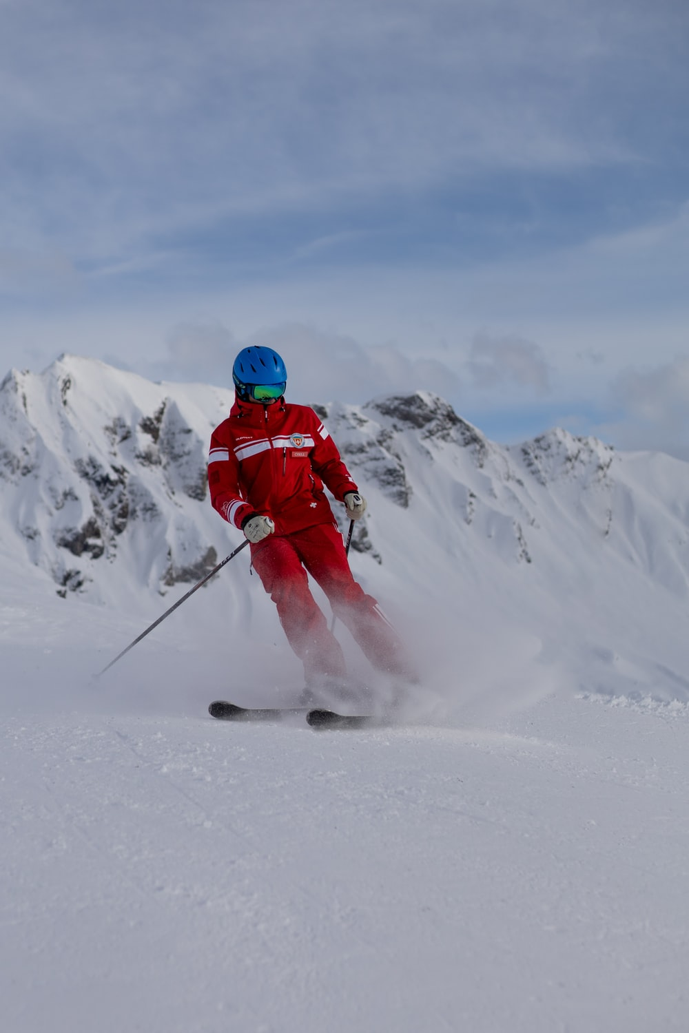 person in red jacket and blue helmet standing on snow covered ground during daytime