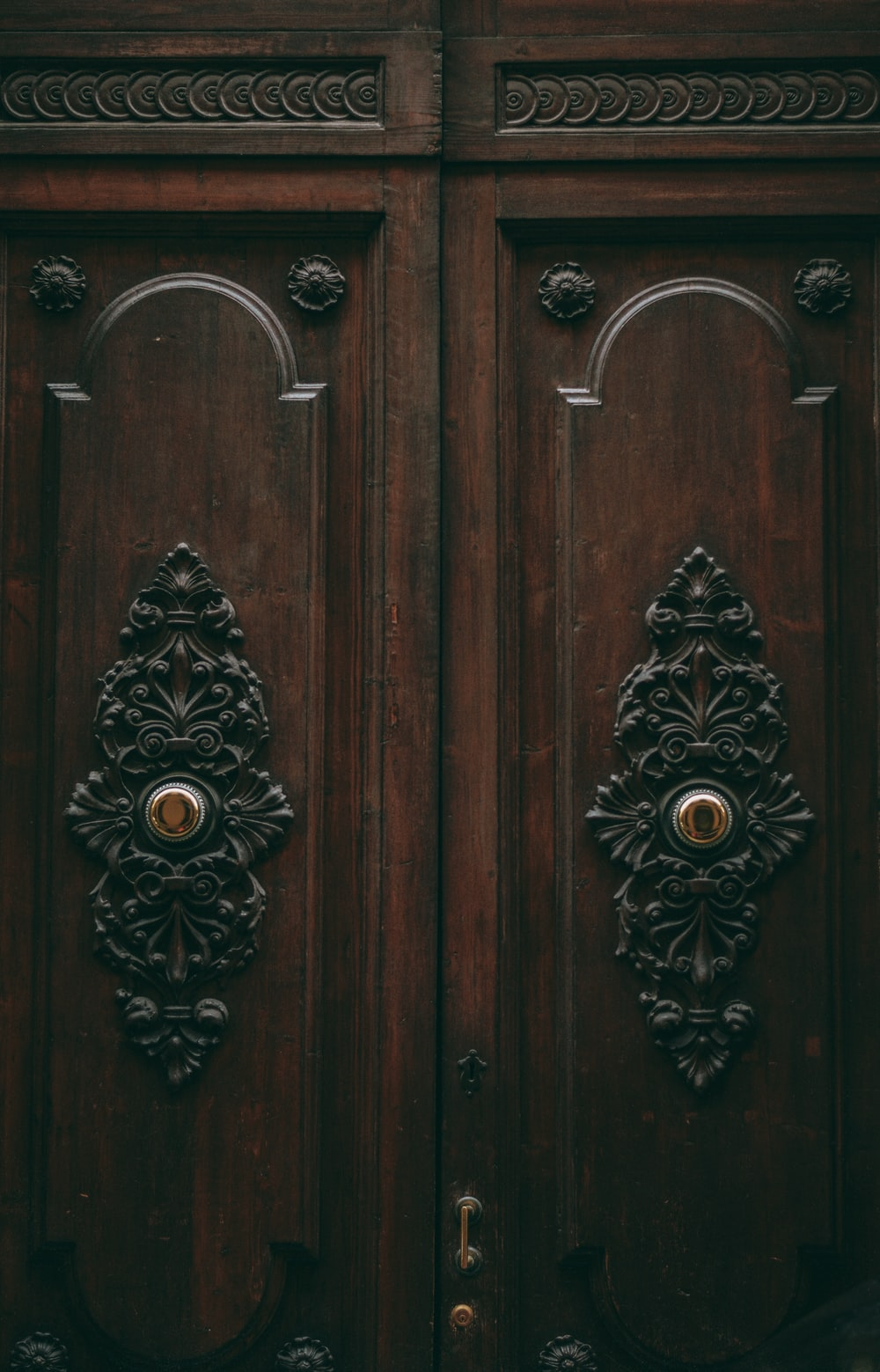 brown wooden door with black and white floral door handle