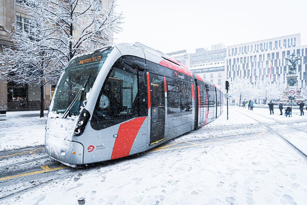 white and red train on snow covered ground during daytime