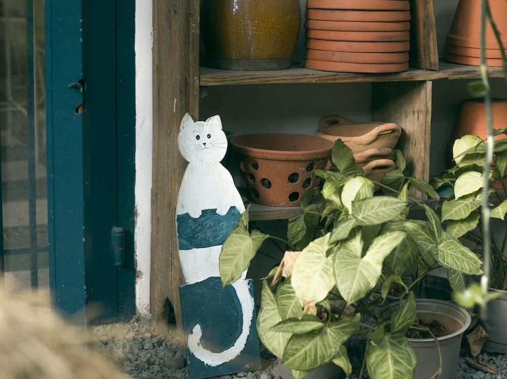 white snowman figurine beside brown wooden window
