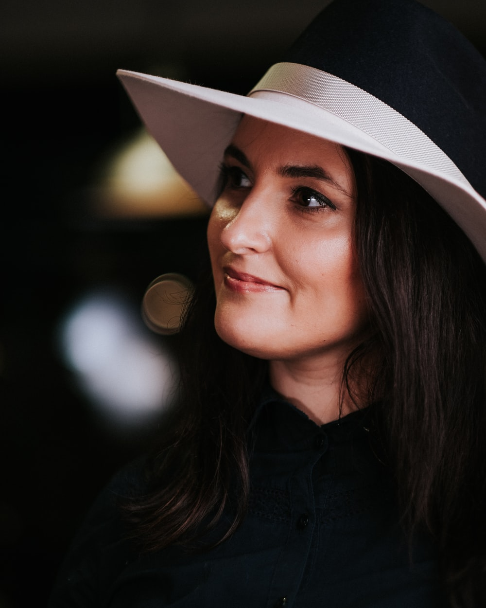 woman in black button up shirt wearing white fedora hat